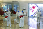 Cleaners in hazmat suits demonstrate disinfection as workers remodel a display window at Siam Paragon, an upmarket shopping mall in Bangkok, Thailand, Thursday, May 14, 2020. Shopping malls in Thailand are preparing to reopen, almost two months after authorities ordered them closed in the fight against the COVID-19 pandemic. (AP Photo/ Gemunu Amarasinghe)