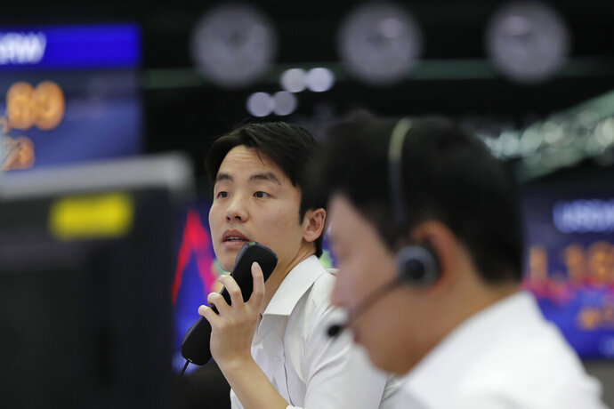 A currency trader holds a phone at the foreign exchange dealing room in Seoul, South Korea, Thursday, Nov. 7, 2019. Asian stocks are mostly lower after a meandering day of trading left U.S. stock indexes close to their record highs. (AP Photo/Lee Jin-man)