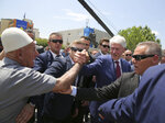 Former U.S. President Bill Clinton, center right, shakes hands with an elderly ethnic Albanian wears his traditional cap during anniversary celebrations in the capital Pristina, Kosovo, Wednesday, June 12, 2019. It's exactly 20 years since NATO forces set foot in the former Yugoslav province, after an allied bombing campaign ended Serbia's bloody crackdown on an insurrection by the majority ethnic Albanian population in Kosovo _ revered by Serbs as their historic and religious heartland. (AP Photo/Visar Kryeziu)