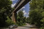 A motorist drives under the CSX Transportation tracks where several separate, more stableencampments on Willow Street face relocation, on Friday, July 16, 2021, in Athens, Ga. (Kayla Renie/Athens Banner-Herald via AP)