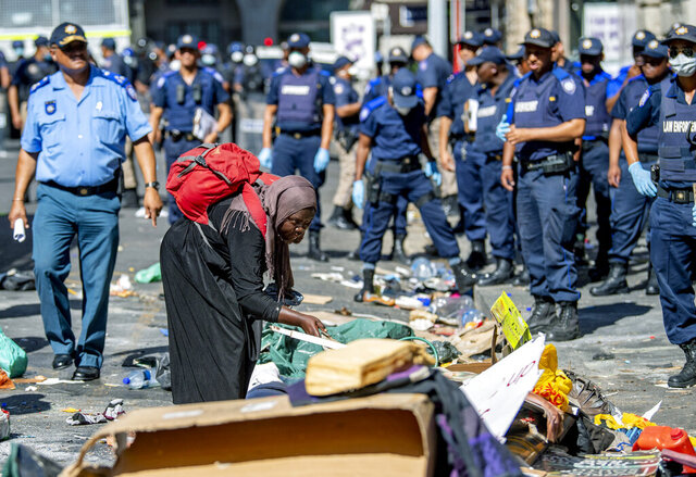 A woman sorts out her belongings, outside the Central Methodist Mission Church in Cape Town, South Africa, Sunday, March 1, 2020 as city officials and police move in to evict them. Hundreds of migrants have been removed from central Cape Town by South African authorities following a months-long stand-off. The migrants removed on Sunday had demanded to be relocated to other countries claiming they had been threatened by xenophobic violence last year.  (AP Photo)