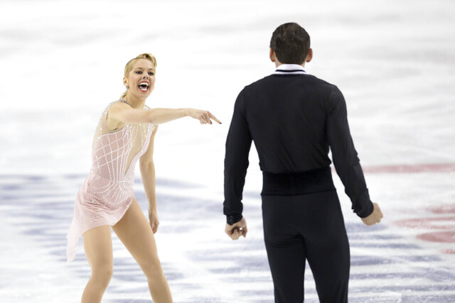 Alexa Knierim reacts pointing to Christopher Knierim at the completion of their program in the senior pairs at the U.S. Figure Skating Championships Thursday, Jan. 23, 2020 in Greensboro, N.C. They are in currently in first place after the program. (AP Photo/Lynn Hey)
