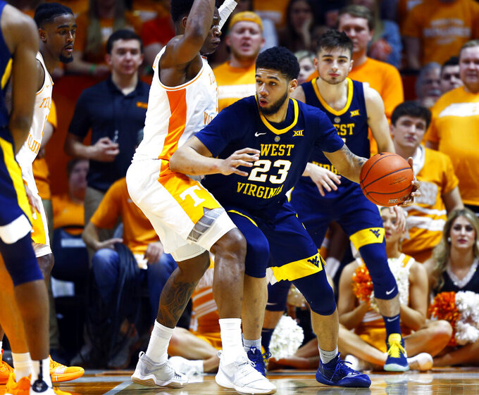 West Virginia forward Esa Ahmad (23) works for a shot as he's defended by Tennessee guard Admiral Schofield (5) in the first half of an NCAA college basketball game Saturday, Jan. 26, 2019, in Knoxville, Tenn. (AP Photo/Wade Payne)