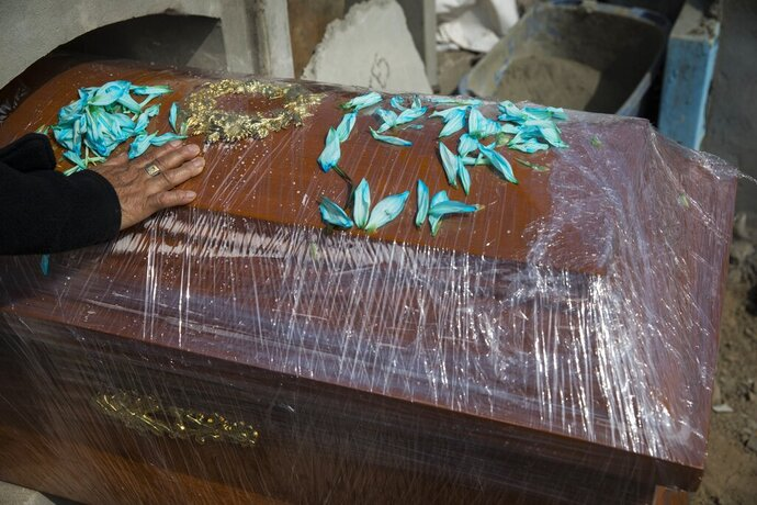 A relative of Joaquin Alonso touches the coffin of the 58-year-old who died of COVID-19 during his burial at the cemetery