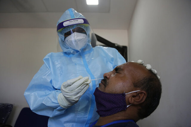 An Indian health worker takes a nasal swab sample of roadside vendor at a health center in Ahmedabad, India, Wednesday, July 8, 2020. India has overtaken Russia to become the third worst-affected nation by the coronavirus pandemic. (AP Photo/Ajit Solanki)