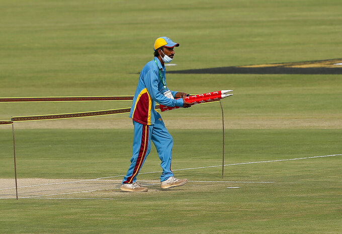 A member of ground staff removes wickets in the Pindi Cricket Stadium following cancel of 1st one day international cricket match between Pakistan and New Zealand, in Rawalpindi, Pakistan, Friday, Sept. 17, 2021. The limited-overs series between Pakistan and New Zealand has been postponed due to security concerns of the Kiwis. (AP Photo/Anjum Naveed)