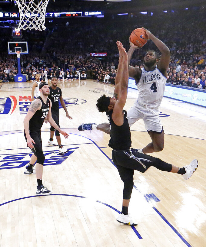 Villanova forward Eric Paschall (4) goes up for a shot against Xavier guard Paul Scruggs during the second half of an NCAA college basketball semifinal game in the Big East men's tournament, Friday, March 15, 2019, in New York. (AP Photo/Julio Cortez)