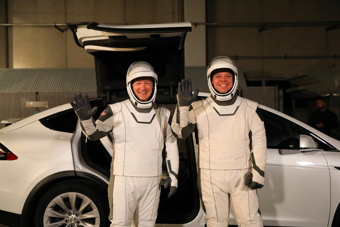 In this Friday, Jan. 17, 2020, photo provided by NASA, astronauts Doug Hurley, left, and Robert Behnken pose in front of a Tesla Model X at a SpaceX launch dress rehearsal, at Kennedy Space Center, in Florida. The NASA astronauts rode to the pad in the Tesla. (Kim Shiflett/NASA via AP)