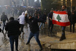 Anti-government demonstrators throw stones toward riot police during a protest against a vote of confidence for the new government in downtown Beirut, Lebanon, Tuesday, Feb. 11, 2020. (AP Photo/Bilal Hussein)