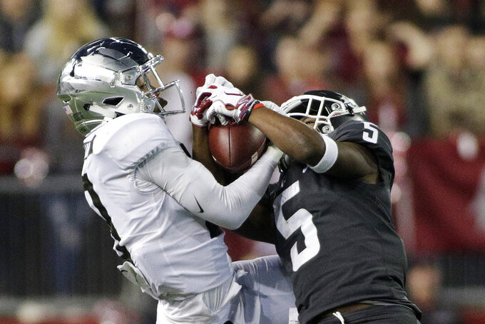 Washington State wide receiver Travell Harris (5) catches a pass while defended by Oregon safety Jevon Holland during the second half of an NCAA college football game in Pullman, Wash., Saturday, Oct. 20, 2018. Washington State won 34-20. (AP Photo/Young Kwak)
