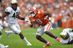 Clemson's Travis Etienne (9) rushes while defended by Wake Forest's Chase Jones during the first half of an NCAA college football game Saturday, Nov. 16, 2019, in Clemson, S.C. (AP Photo/Richard Shiro)