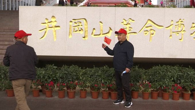 A tourists holds a flag as he poses for photographs in front of the sign for the Jinggangshan Revolution Museum in Jinggangshan in southeastern China's Jiangxi province, on April 8, 2021. On the hundredth anniversary of the Chinese Communist Party, tourists in China are flocking to historic sites and making pilgrimages to party landmarks. (AP Photo/Emily Wang)