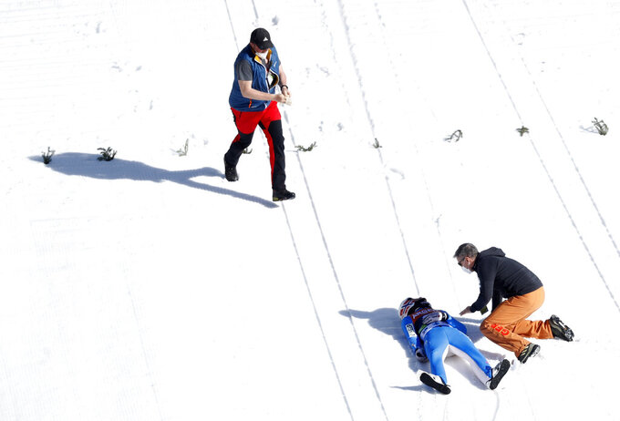 Norway's Daniel Andre Tande lies on snow after crashing during the ski flying individual World Cup event in Planica, Slovenia, Thursday, March 25, 2021. (AP Photo)