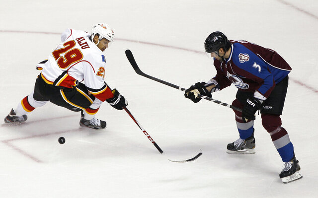 FILE - In this Feb. 28, 2013, file photo, Calgary Flames right wing Akim Aliu loses control of the puck as the blade of his stick breaks off, while Colorado Avalanche's Ryan O'Byrne defends during the first period of an NHL hockey game in Denver. Former NHL forward Aliu expects
