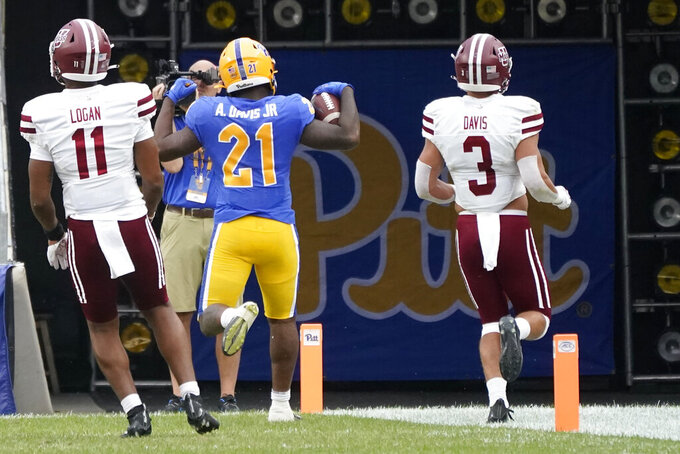 Pittsburgh running back A.J. Davis Jr. (21) celebrates as he out runs Massachusetts safety Tanner Davis (3) and linebacker Nahji Logan (11) for a touchdown during the first half of an NCAA college football game, Saturday, Sept. 4, 2021, in Pittsburgh. (AP Photo/Keith Srakocic)