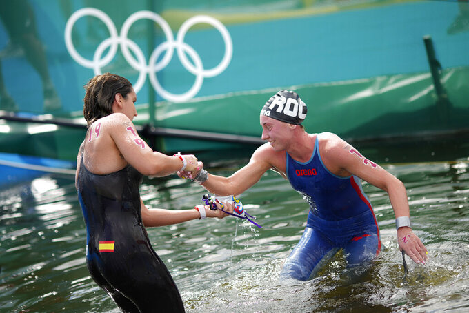Paula Ruiz Bravo, of Spain, left, helps up Anastasiia Kirpichnikova, of the Russian Olympic Committee, after they finished in the women's marathon swimming event at the 2020 Summer Olympics, Wednesday, Aug. 4, 2021, in Tokyo. (AP Photo/David Goldman)