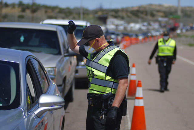 FILE - In this May 7, 2020, file photo, New Mexico state police officers screen cars for compliance with an emergency lockdown order that bans nonessential visitors and limits vehicle passengers to two people as they enter Gallup, N.M. From lockdowns in tribal communities to the economic and social fallout reverberating through every facet of life in New Mexico, the coronavirus pandemic dominated headlines in 2020. COVID-19 infections were on track to top 140,000 by the end of the year, with the curve taking its steepest rise in November as part of what state health officials described as the third surge to hit New Mexico. (AP Photo/Morgan Lee, File)