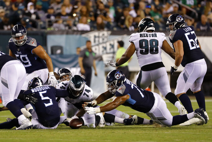 Tennessee Titans' Logan Woodside (5) fumbles the ball as Philadelphia Eagles' Daeshon Hall (74) and Titans' Jamil Douglas (75) try to recover it during the second half of a preseason NFL football game Thursday, Aug. 8, 2019, in Philadelphia. (AP Photo/Michael Perez)
