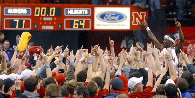 FILE - In this Feb. 20, 2008, file photo, Nebraska's Cookie Miller (24) body surfs the crowd that rushed the court after Nebraska beat Kansas State 71-64 in a college basketball game in Lincoln, Neb. When the virus wanes enough to allow the games to begin again, the very essence of these events will likely be missing. Playing in empty buildings would require a significant recalibration.(AP Photo/Dave Weaver, FIle)