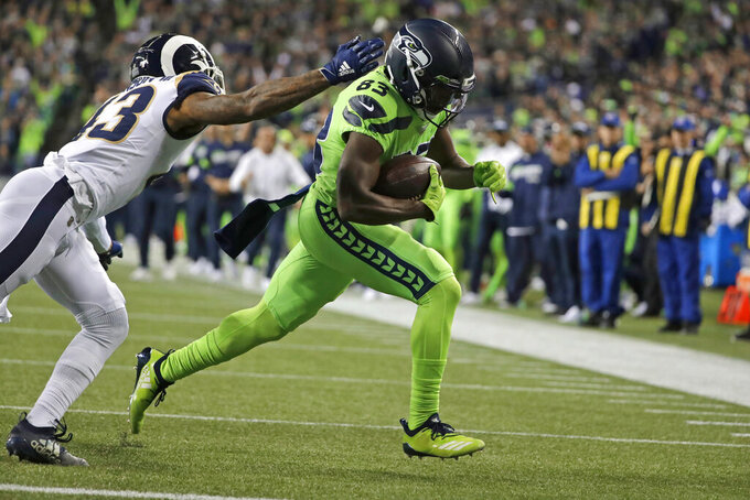 Seattle Seahawks wide receiver David Moore, right, gets past Los Angeles Rams strong safety John Johnson to score a touchdown during the second half of an NFL football game Thursday, Oct. 3, 2019, in Seattle. (AP Photo/Elaine Thompson)