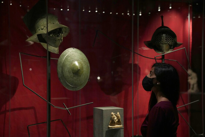 """A museum employee poses for photographers next to Roman era gladiatorial helmets and a shield, during a media preview for the """"Nero: the man behind the myth"""" exhibition, at the British Museum in London, Monday, May 24, 2021. The exhibition, which open to visitors on May 27 and runs until October 24, explores the true story of Rome's fifth emperor informed by new research and archaeological evidence from the time. (AP Photo/Matt Dunham)"""
