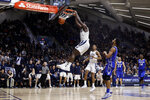 Villanova's Eric Paschall hangs off the rim after a dunk past Creighton's Davion Mintz during overtime in an NCAA college basketball game Wednesday, Feb. 6, 2019, in Villanova, Pa. Villanova won 66-59. (AP Photo/Matt Slocum)