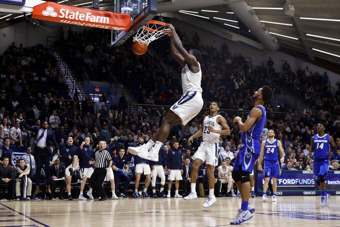 Villanova's Eric Paschall hangs off the rim after a dunk past Creighton's Davion Mintz during overtime in an NCAA college basketball game Wednesday, Feb. 6, 2019, in Villanova, Pa. Villanova won 66-59. (AP Photo/Matt Slocum)
