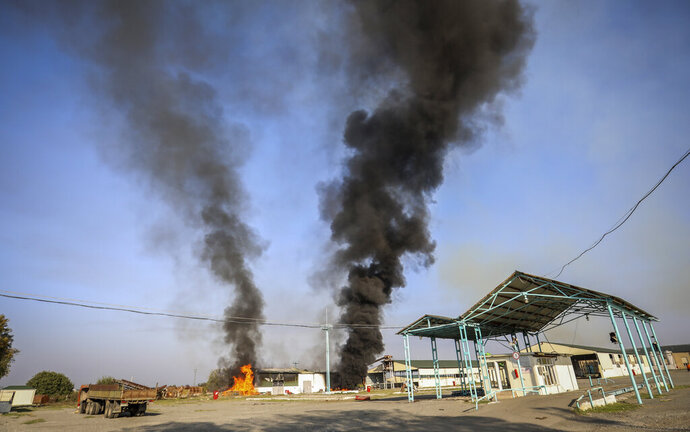 A view of a fire in the territory of local factory following recent shelling during fighting over the separatist region of Nagorno-Karabakh, in Terter, Azerbaijan, Monday, Oct. 19, 2020. Reports of renewed shelling on Monday challenged the new cease-fire in the conflict over the separatist territory of Nagorno-Karabakh, where heavy fighting between Armenian and Azerbaijani forces has raged for over three weeks. (AP Photo/Aziz Karimov)