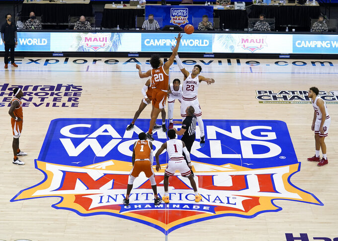 Texas forward Jericho Sims (20) and Indiana forward Trayce Jackson-Davis (23) tip off for the start of a semifinal NCAA college basketball game in the Maui Invitational tournament, Tuesday, Dec. 1, 2020, in Asheville, N.C. (AP Photo/Kathy Kmonicek)