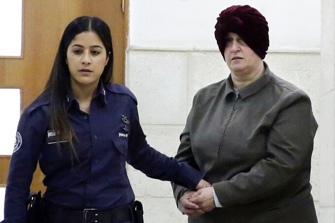 FILE - This Feb. 27, 2018, file photo, Israeli-born Australian Malka Leifer, right, is brought to a courtroom in Jerusalem. A former school counsellor testified in an Australian court from Israel on Monday that she suspected two sisters alleged they had been sexually abused by Leifer in an attempt to get financial compensation. (AP Photo/Mahmoud Illean, File)