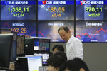 A currency trader smiles at the foreign exchange dealing room of the KEB Hana Bank headquarters in Seoul, South Korea, Wednesday, March 25, 2020. Shares have advanced in Asia after the Dow Jones Industrial Average surged to its best day since 1933 as Congress and the White House neared a deal to inject nearly $2 trillion of aid into an economy ravaged by the coronavirus. (AP Photo/Ahn Young-joon)