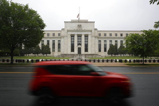 File-In this May 22, 2020, file photo, a car drives past the Federal Reserve building in Washington. The Federal Reserve on Sunday, June 28, 2020, released a list of roughly 750 companies, including Apple, Walmart, and ExxonMobil, whose corporate bonds it will purchase in the coming months in an effort to keep borrowing costs low and smooth the flow of credit.  The central bank also said it has, so far, purchased nearly $429 million in corporate bonds from 86 of those companies, including AT&T, Walgreen's, Microsoft, Pfizer, and Marathon Petroleum. (AP Photo/Patrick Semansky, File)