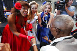 The Victory Belles hold the hands of World War II veteran Lawrence Brooks as they sing him happy birthday celebrating his 110th birthday at the National World War II Museum in New Orleans, Thursday, Sept. 12, 2019. Brooks was born Sept. 12, 1909, and served in the predominantly African-American 91st Engineer Battalion, which was stationed in New Guinea and then the Philippines during World War II. He was a servant to three white officers in his battalion. (AP Photo/Gerald Herbert)