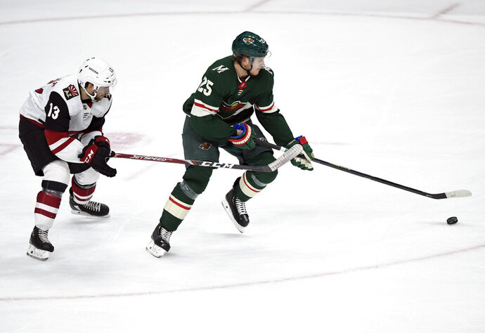 Minnesota Wild's Jonas Brodin (25), of Sweden, works with the puck next to Arizona Coyotes' Vinnie Hinostroza (13) during the first period of an NHL hockey game Thursday, Nov. 14, 2019, in St. Paul, Minn. (AP Photo/Hannah Foslien)