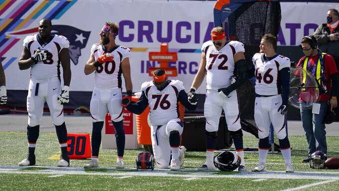 Members of the Denver Broncos team kneel and stand during the national anthem before an NFL football game against the New England Patriots, Sunday, Oct. 18, 2020, in Foxborough, Mass. (AP Photo/Charles Krupa)