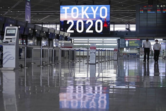 Staff wearing protective masks to help curb the spread of the coronavirus walk in the empty ticketing area at Narita International Airport Tuesday afternoon, June 1, 2021, in Narita, east of Tokyo. A state of emergency in Tokyo, Osaka and other prefectures was last week extended until June 20 as COVID-19 cases continue to put the medical system under strain. (AP Photo/Eugene Hoshiko)