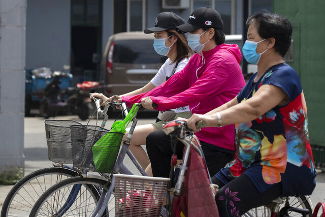 Residents wearing masks to curb the spread of the coronavirus ride past a neighborhood under lockdown in Beijing Tuesday, June 16, 2020. Chinese authorities locked down a third neighborhood in Beijing on Tuesday as they rushed to prevent the spread of a new coronavirus outbreak that has infected more than 100 people in a country that appeared to have largely contained the virus. (AP Photo/Ng Han Guan)