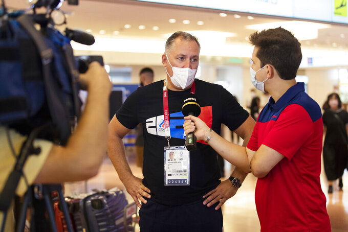 Stanislav Pozdnyakov, president of the Russian Olympic Committee, responds to a Russian reporter's question as he arrives for the Tokyo 2020 Summer Olympic and Paralympic Games at Haneda international airport in Tokyo on Sunday, July 18, 2021. (AP Photo/Hiro Komae)