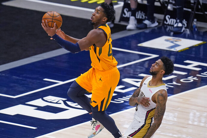 Utah Jazz guard Donovan Mitchell, left, goes to the basket as New Orleans Pelicans guard Nickeil Alexander-Walker defends during the first half of an NBA basketball game Tuesday, Jan. 19, 2021, in Salt Lake City. (AP Photo/Rick Bowmer)