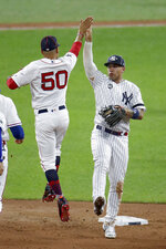 American League's Gleyber Torres, of the New York Yankees, and Mookie Betts (50), of the Boston Red Sox, celebrate the American League's 4-3 victory over the National League in the MLB baseball All-Star Game, Tuesday, July 9, 2019, in Cleveland. (AP Photo/Ron Schwane)
