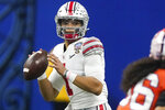 FILE - In this Friday, Jan. 1, 2021, file photo, Ohio State quarterback Justin Fields passes against Clemson during the second half of the Sugar Bowl NCAA college football game in New Orleans. Ohio State quarterback Justin Fields was among 98 juniors granted eligibility by the NFL into the draft, while national championship-winning QBs Mac Jones from Alabama and Trevor Lawrence from Clemson were among another 30 players eligible after completing their degrees and deciding not to play more in college.  (AP Photo/John Bazemore, File)