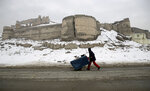 An Afghan street vendor pulls his hand cart after a heavy snowfall in Kabul, Afghanistan, Tuesday, Jan. 14, 2020. Severe winter weather has struck parts of Afghanistan and Pakistan, with heavy snowfall, rains and flash floods that left dozens 40 dead, officials said Monday as authorities struggled to clear and reopen highways and evacuate people to safer places. (AP Photo/Rahmat Gul)
