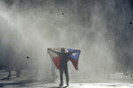 An anti-government protester holds out Chilean flag during clashes with police in Valparaiso, Chile, Friday, Oct. 25, 2019. A new round of clashes broke out Friday as demonstrators returned to the streets, dissatisfied with economic concessions announced by the government in a bid to curb a week of deadly violence.(AP Photo/Matias Delacroix)