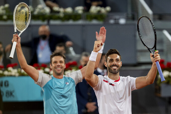 Spain's Marcel Granollers, right, and Horacio Zeballos of Argentina celebrate after winning the men's doubles final match against Croatia's Nikola Mektic and Mate Pavic at the Mutua Madrid Open tennis tournament in Madrid, Spain, Sunday, May 9, 2021. (AP Photo/Bernat Armangue)