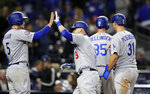 Los Angeles Dodgers' Yasmani Grandal, second from left, is greeted by teammate Corey Seager, left, after hitting a grand slam during the ninth inning of a baseball game against the San Diego Padres, Monday, April 16, 2018, in San Diego. (AP Photo/Gregory Bull)