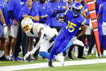 Los Angeles Rams wide receiver Tutu Atwell (15) runs after a reception past Los Angeles Chargers defensive back Nasir Adderley (24) during the first half of a preseason NFL football game Saturday, Aug. 14, 2021, in Inglewood, Calif. (AP Photo/Ringo Chiu )