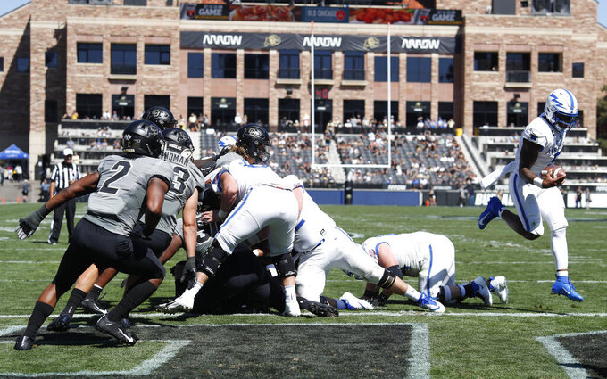 Air Force quarterback Donald Hammond III, far right, jumps past a pile of players to score a touchdown in the first half of an NCAA college football game against Colorado, Saturday, Sept. 14, 2019, in Boulder, Colo. (AP Photo/David Zalubowski)