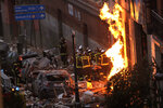 Fire-fighters carry a dead body next to a damaged building at Toledo Street following an explosion in downtown Madrid, Spain, Wednesday, Jan. 20, 2021. A powerful explosion apparently caused by a gas leak has ripped the facade off a residential building in central Madrid. (AP Photo/Manu Fernandez)