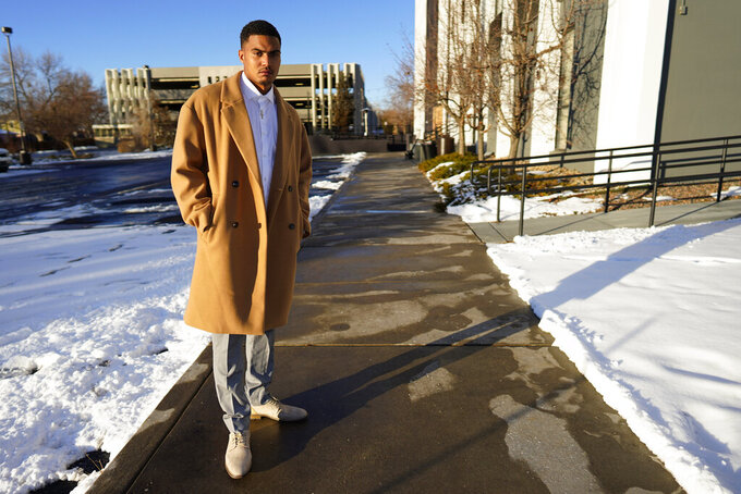 Donte Westmoreland poses for a photo outside a hotel Tuesday, Dec. 15, 2020, in southeast Denver. Westmoreland was recently released from Lansing Correctional Facility in Kansas, where he caught the virus while serving time on a marijuana charge. Some 5,000 prisoners have become infected in Kansas prisons, the second-highest COVID-19 rate in the country, second only to South Dakota. (AP Photo/David Zalubowski)