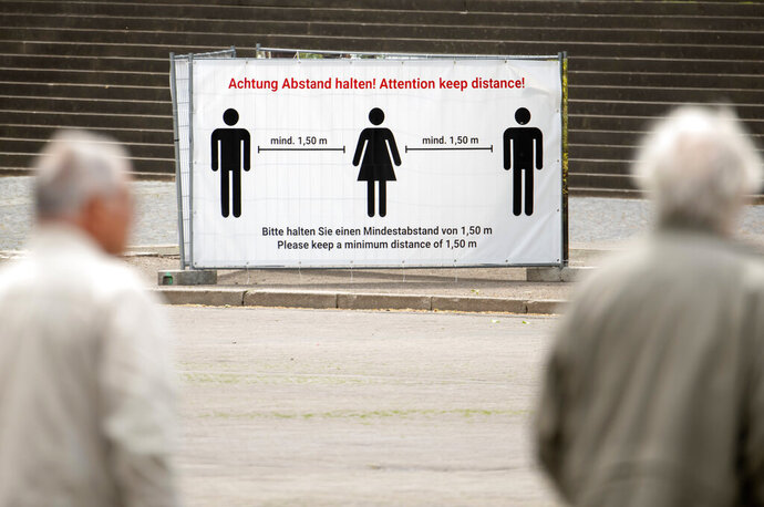 People walk in front of a poster wall displaying the distance rules at the cathedral place in Erfurt, central Germany, Monday, May 25, 2020. A spat is brewing between Germany's federal government and state governors over plans by some regional leaders to end pandemic-related restrictions despite fresh clusters of cases across the country. The governor of Thuringia state, Bodo Ramelow, said Saturday that he hopes to lift the remaining statewide lockdown rules on June 6 and tackle outbreaks locally. (AP Photo/Jens Meyer)